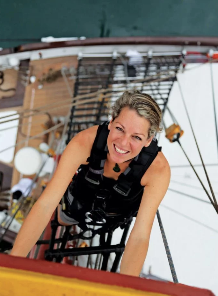WOMAN SMILING ABOVE THE MAST